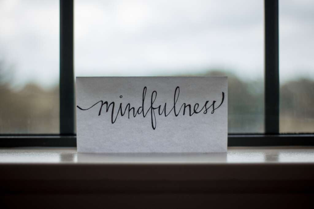 """A piece of paper resting in a windowsill, with the word """"mindfulness"""" written in calligraphy"""