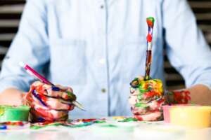 Person with paint covered hands holding a pen and a paintbrush
