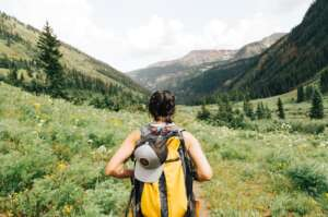 Person with a backpack on facing a forest trail