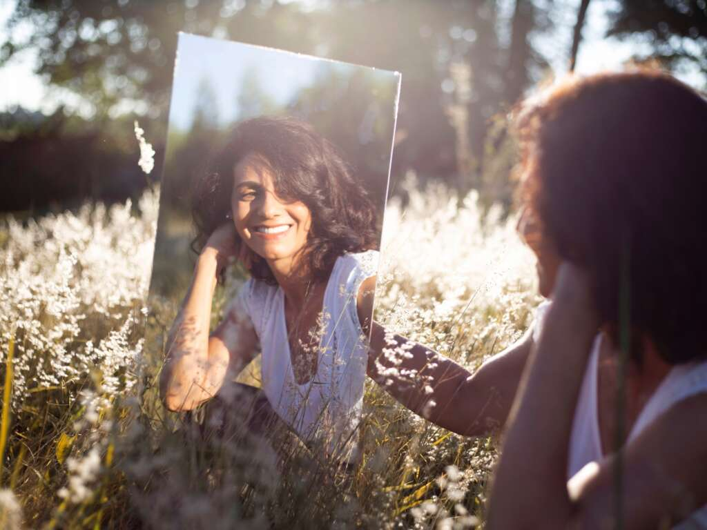 A person smiling in a mirror in a field
