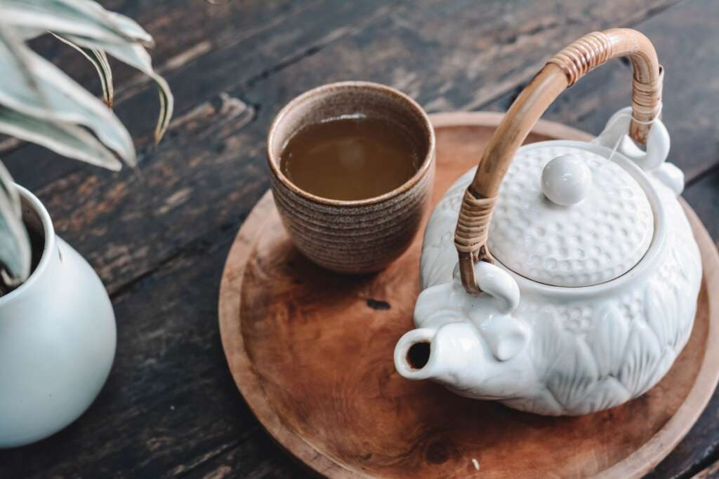 Teapot next to cup of tea and a plant