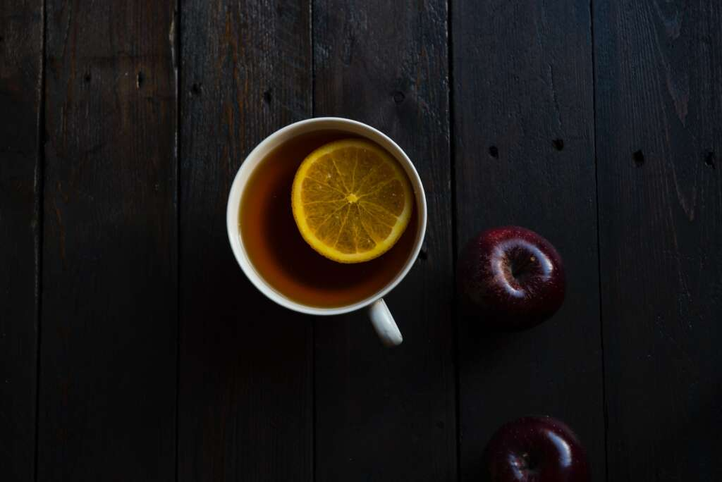Teacup with a lemon slice in the tea, next to apples